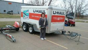 woman standing next to rentable u-haul trailer