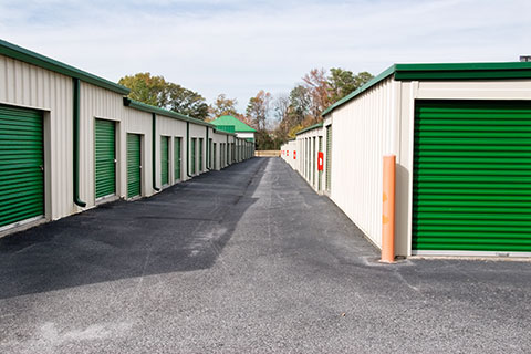 Residential storage units with green doors.