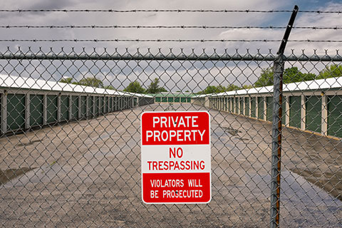 No trespassing sign on a barbed wire fence with secure storage units in the background.