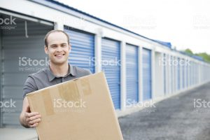 White balding man smiling and holding a large cardboard box in front of a row of blue storage units.