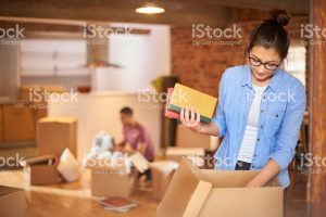 woman packing boxes with books and posessions